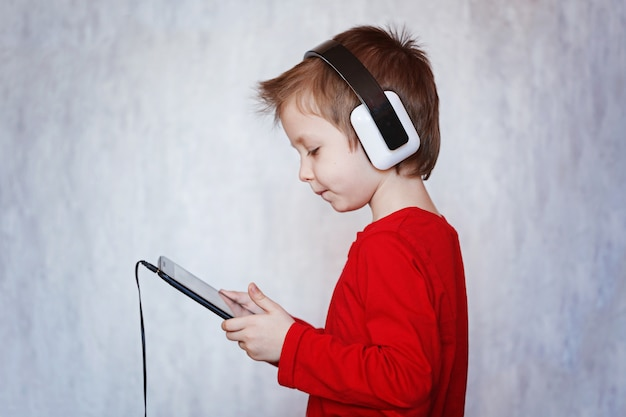 Menino da criança que escuta a música ou que olha o filme com fones de ouvido e que usa a tabuleta digital.