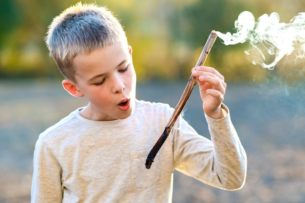 Menino da criança que joga com fumo a vara de madeira ao ar livre.