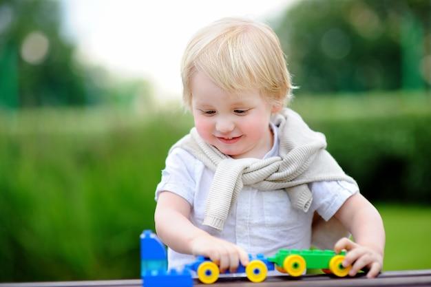 Menino da criança que joga com trem do brinquedo fora no dia de verão morno. brinquedos para criancinhas