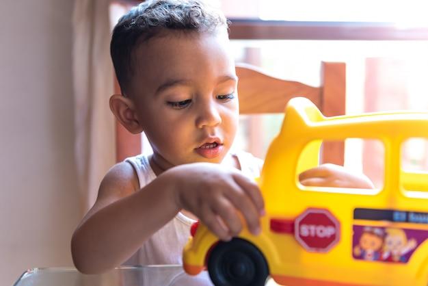 Menino da criança que joga com um brinquedo do ônibus escolar dentro.