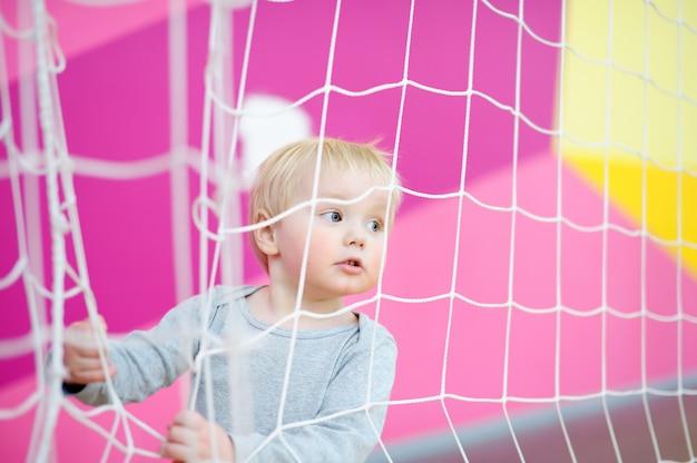 Menino da criança que joga na quadra de esporte dentro de casa