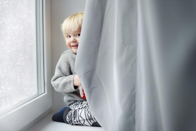 Menino da criança que joga no peitoril da janela em casa