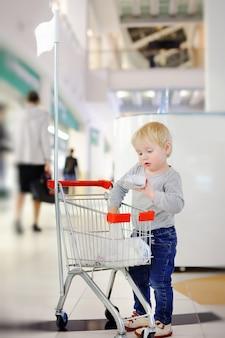 Menino da criança que põe a compra no carrinho de compras pequeno em um shopping