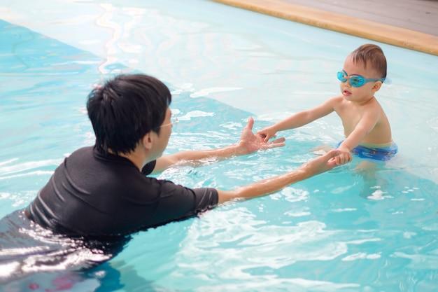 Menino da criança usar óculos de natação jogando na piscina interior com seu pai