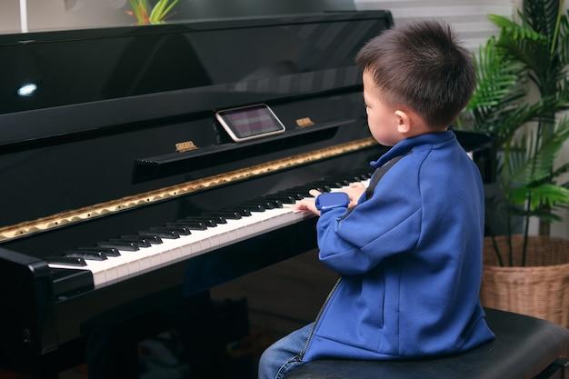Menino da escola de jardim de infância asiático aprendendo a tocar piano usando o smartphone com uma aula on-line e um curso na sala de estar em casa