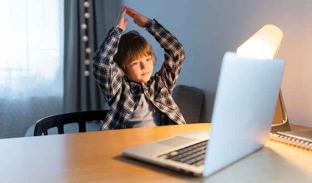 Menino da escola fazendo cursos online e gesticulando