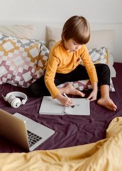 Menino da escola sentado na cama e aprende