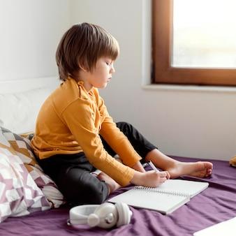 Menino da escola sentado na cama, vista lateral