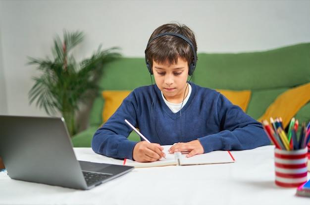 Menino da escola tendo aulas online enquanto está sentado em casa na quarentena, usando laptop e fazendo anotações