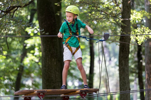 Menino da jovem criança no chicote de fios e capacete unidos com carabina ao cabo na maneira da corda no parque.