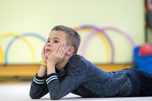 Menino da jovem criança que estabelece e relaxiong ao descansar no assoalho dentro da sala de esportes em uma escola após o treinamento.