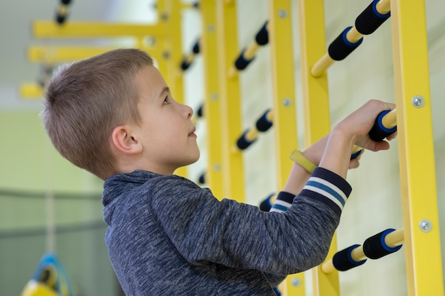 Menino da jovem criança que exercita em uma barra da escada da parede dentro da sala do gym dos esportes em uma escola.