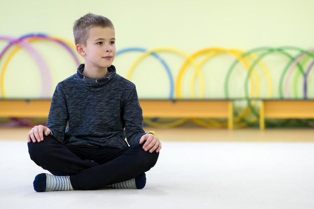 Menino da jovem criança que senta-se e que relaxa no assoalho dentro da sala de esportes em uma escola após o treinamento.