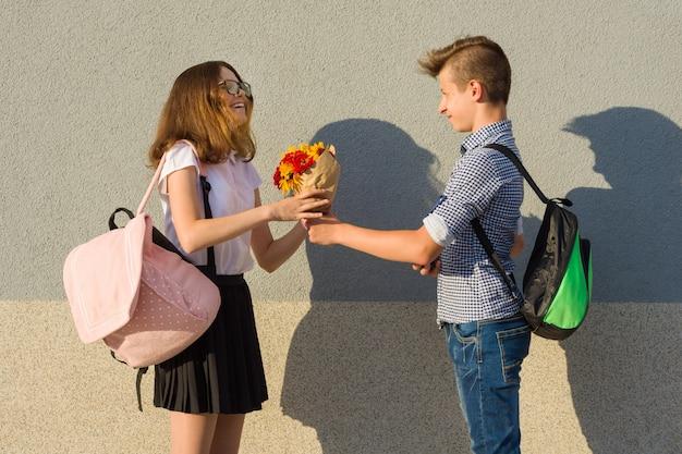 Menino dá, menina, buquê flores