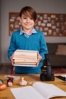 Menino da primeira série estudando em casa, segurando um monte de livros, se preparando para a aula online