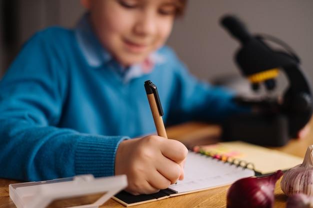 Menino da primeira série estudando em casa usando microscópio