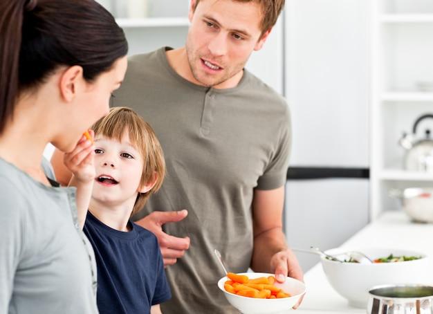 Menino dando a sua mãe uma cenoura enquanto prepara o almoço