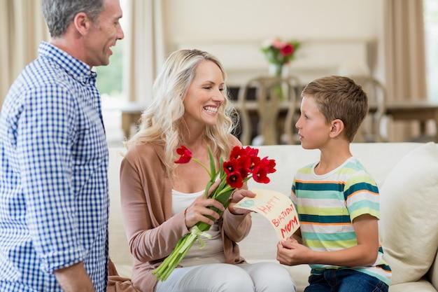 Menino dando cartão e rosas para sua mãe