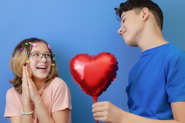 Menino dando um balão vermelho em forma de coração para menina, presente de dia dos namorados