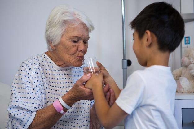 Menino dando um copo d'água para paciente sênior