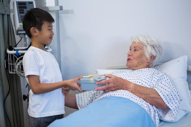 Menino dando um presente para paciente idoso na cama