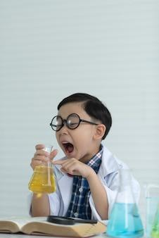 Menino das crianças que estuda a solução química no laboratório usando uns produtos vidreiros.