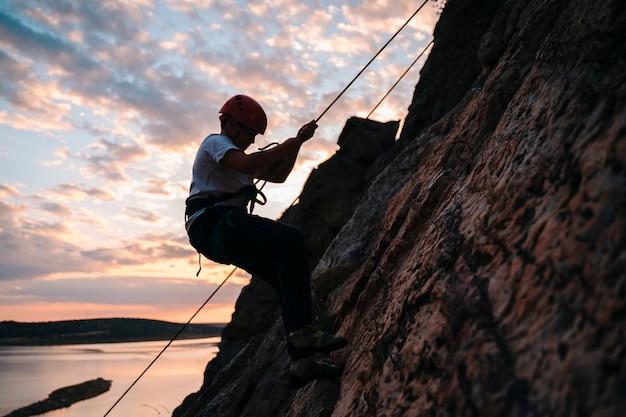Menino de 10 anos descendo de uma montanha ao pôr do sol