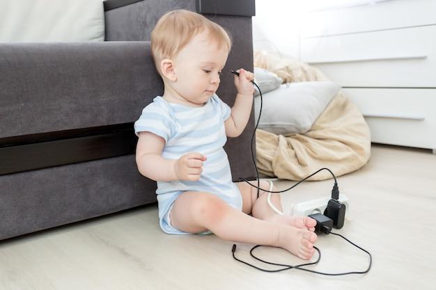 Menino de 10 meses puxando cabos da extensão elétrica
