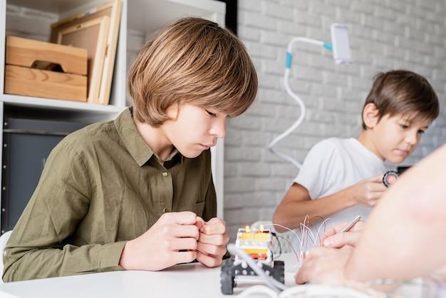 Menino de 12 anos com camisa verde construindo um carro robô na oficina