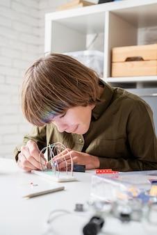 Menino de 12 anos construindo um carro robô sentado à mesa brincando com luzes