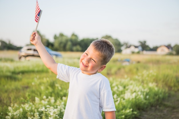 Menino de 4 anos segurando uma bandeira americana ao pôr do sol no campo