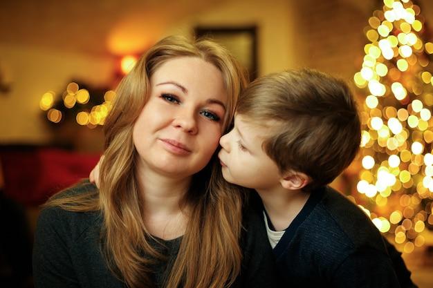 Menino de 5 a 7 anos beija a mãe em um interior festivo de ano novo