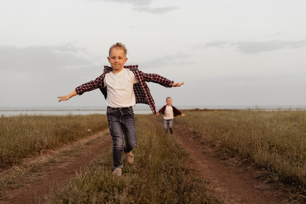 Menino de 5 anos corre na estrada no campo.