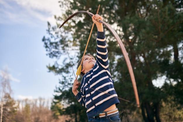 Menino de 6 anos de idade atira um arco ao ar livre