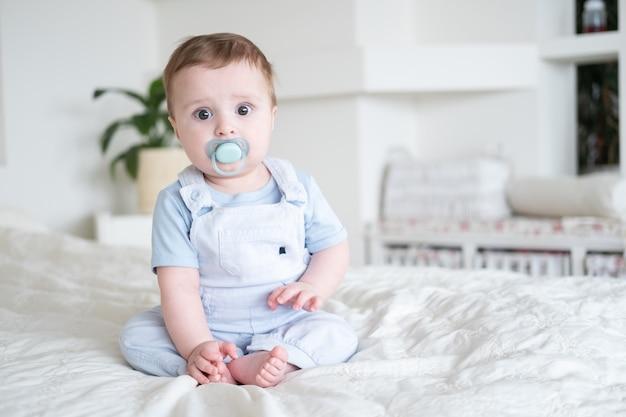 Menino de 6 meses de idade com mamilo em roupas azuis e sentado na cama branca em casa