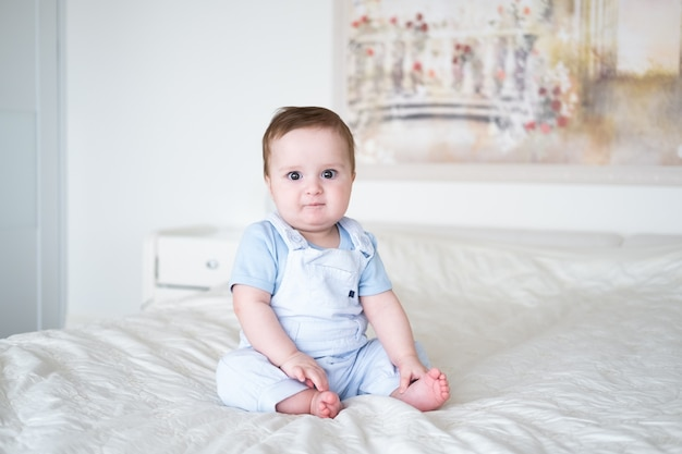 Menino de 6 meses de idade com roupas azuis, sorrindo e sentado na cama branca em casa.
