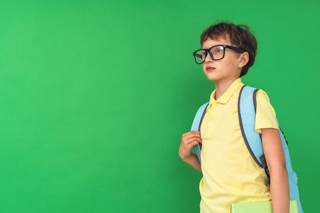 Menino de 7 anos de idade com mochila nas costas, olhando para longe.