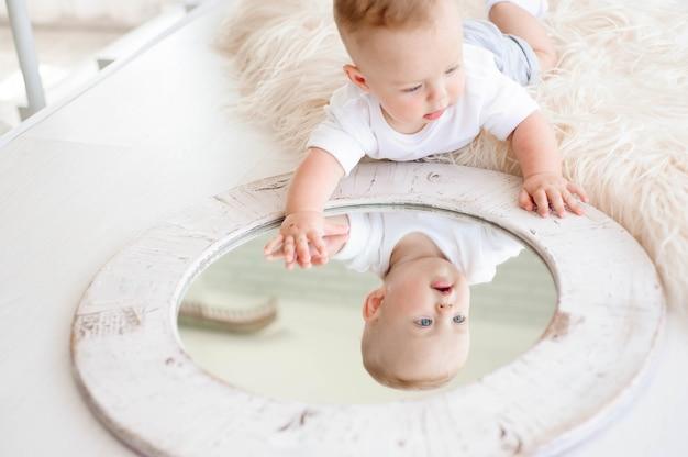 Menino de 7 meses joga no tapete branco no quarto