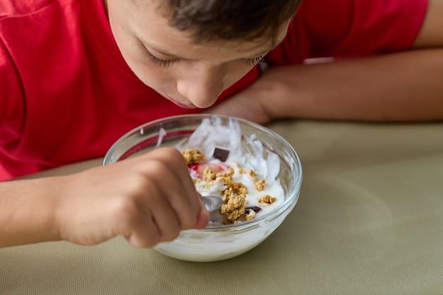 Menino de 8 anos comendo muesli e iogurte com uma camiseta vermelha, aparência de perto