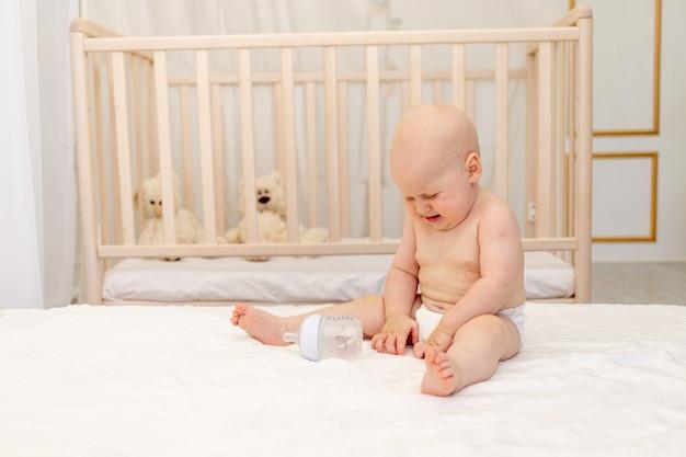 Menino de 8 meses de idade sentado em fraldas em uma cama branca com uma garrafa de leite em casa e chorando, conceito de comida para bebé, primeira isca