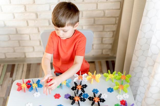 Menino de alto ângulo com brinquedos florais