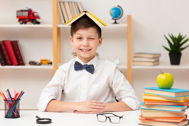 Menino de alto ângulo com o livro na cabeça