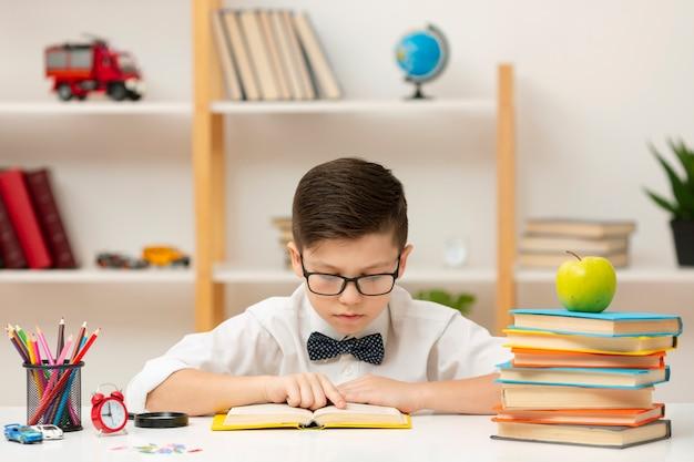 Menino de alto ângulo com óculos de leitura
