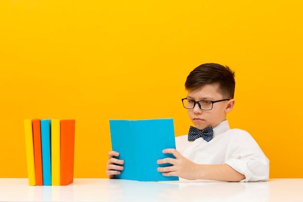 Menino de alto ângulo na leitura do escritório