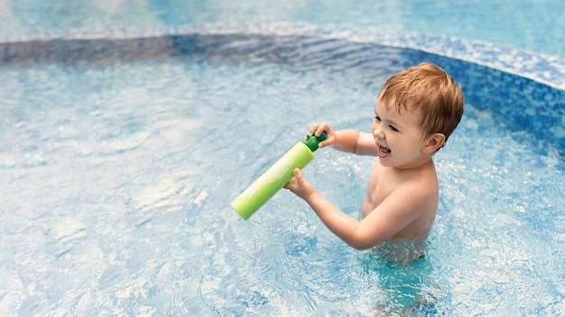 Menino de alto ângulo na piscina brincando com pistola de água