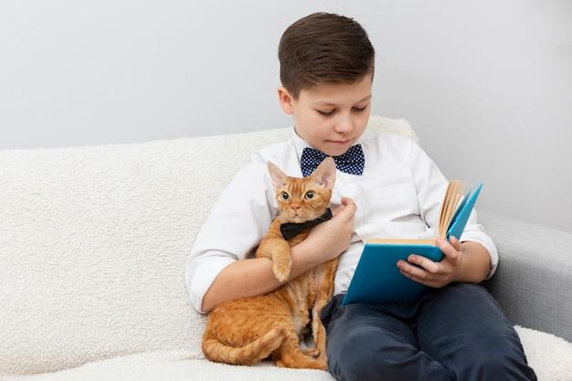 Menino de ângulo alto com leitura de gato