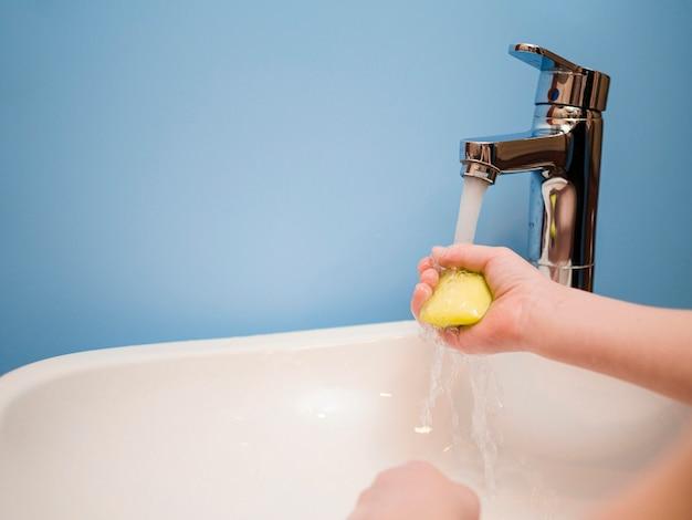 Menino de ângulo alto, lavar as mãos