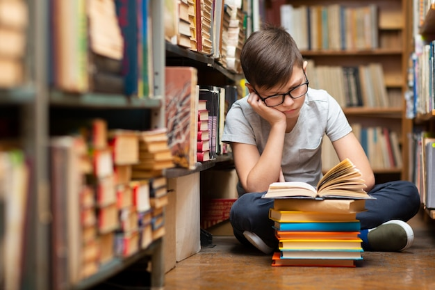 Menino de ângulo alto na leitura da biblioteca