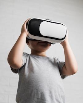 Menino de ângulo baixo, assistindo a realidade virtual