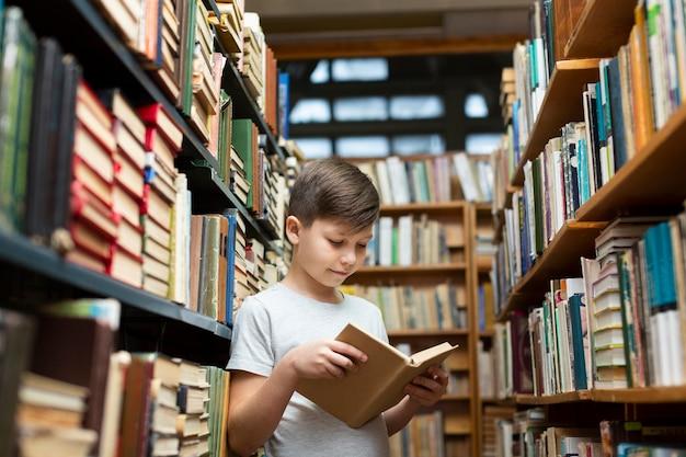Menino de ângulo baixo na leitura da biblioteca